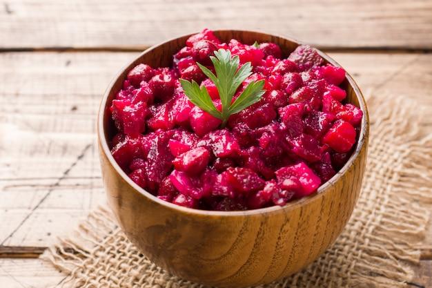 Vinagrete caseiro fresco da salada de beterraba em uma bacia de madeira. comida russa tradicional.