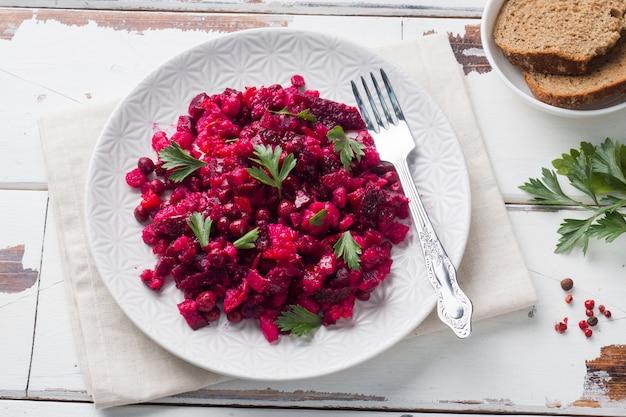 Vinagrete caseiro fresco da salada de beterrabas em uma bacia branca. comida russa tradicional. copie o espaço