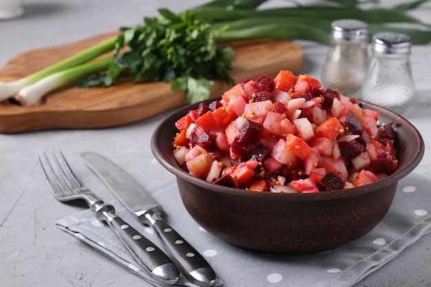 Vinagrete tradicional de salada russa com beterraba, cenoura, batata e cebola em uma tigela de barro contra uma superfície de concreto cinza, comida vegetariana, closeup, formato horizontal