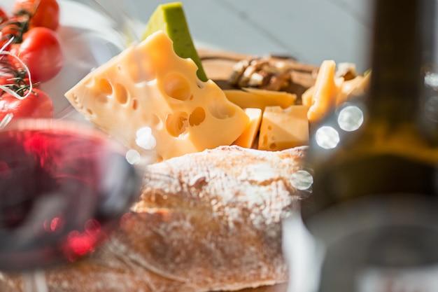 Vinho, baguete e queijo na mesa de madeira