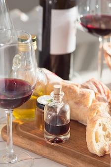 Vinho, baguete e queijo no fundo de madeira