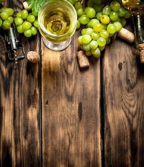 Vinho branco com ramos de uvas brancas. em uma mesa de madeira.