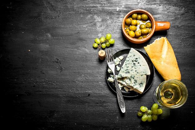 Vinho branco com saboroso queijo e saborosas azeitonas.