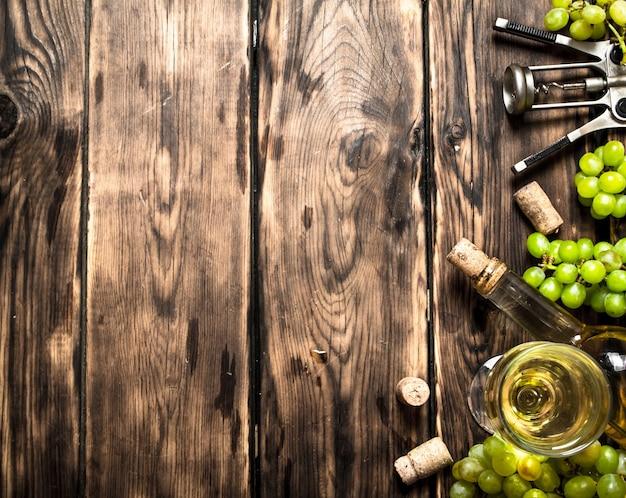 Vinho branco com saca-rolhas e ramos de uvas. em uma mesa de madeira.