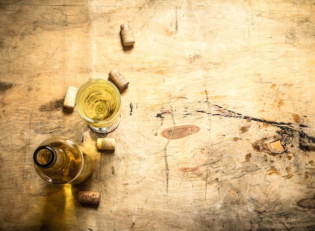 Vinho branco com saca-rolhas e rolhas. em fundo de madeira.