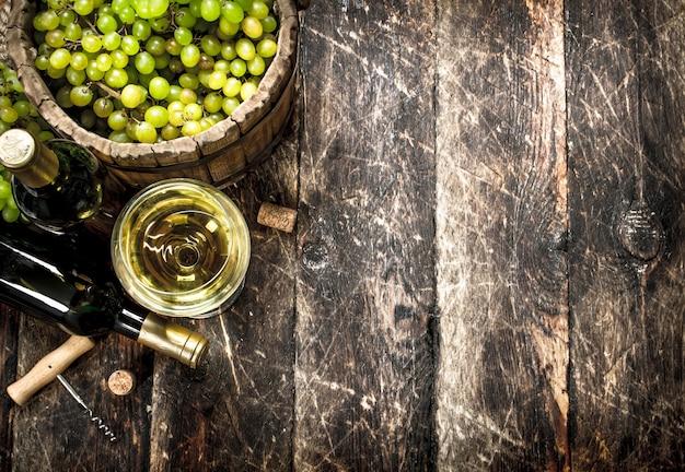Vinho branco com um balde de uvas verdes. em uma mesa de madeira.