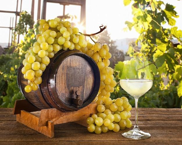 Vinho branco com uvas e barril.
