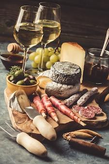 Vinho branco com variedade de charcutaria no fundo de pedra