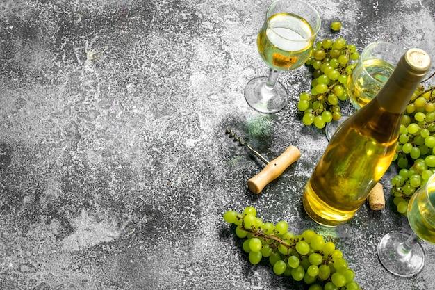 Vinho branco de uvas verdes frescas. sobre uma mesa rústica.