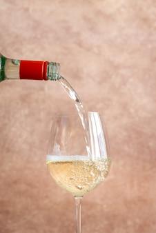 Vinho branco derramando em vidro
