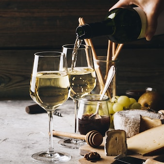 Vinho branco, despejando copos com variedade de charcutaria