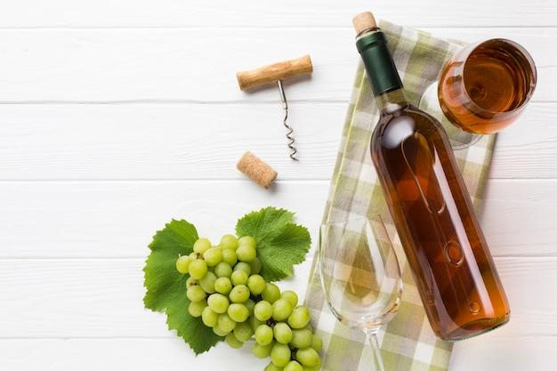 Vinho branco e copos em fundo de madeira