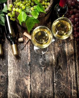 Vinho branco e tinto com ramos de uvas na mesa de madeira.