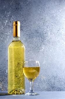 Vinho branco em copos de vinho de vidro, uma garrafa de vinho