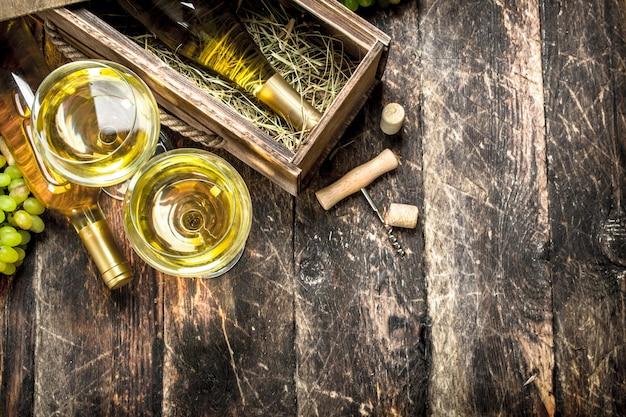 Vinho branco em copos na mesa de madeira.