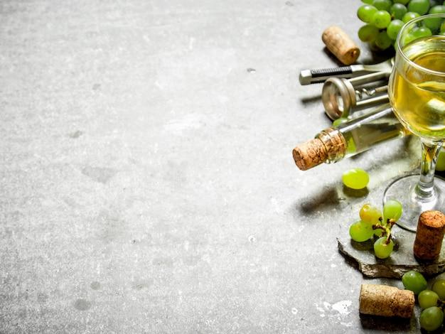 Vinho branco em garrafa e copo. na mesa de pedra.