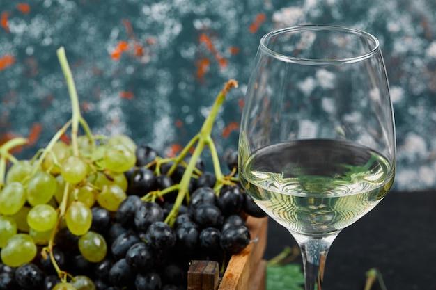 Vinho branco em um copo com um cacho de uvas verdes ao redor.