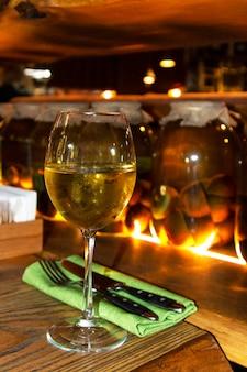Vinho branco em um copo de vidro em um fundo desfocado de frutas enlatadas em um bar escuro. uma taça de vinho de uva