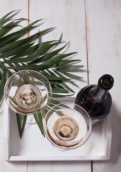 Vinho branco em um óculos, garrafa na bandeja de madeira branca.