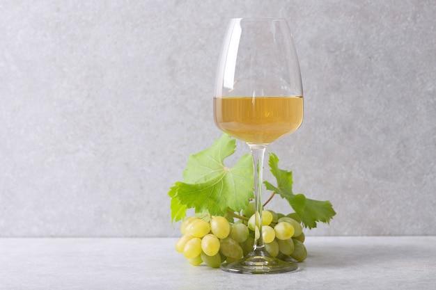 Vinho branco em uma taça e um cacho de uvas na mesa. parede clara.