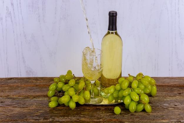 Vinho branco em vidro com um cacho de uvas verdes contra fundo cinza de madeira