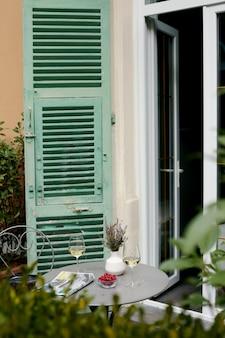 Vinho branco, framboesas frescas e groselhas em uma mesa ao lado de um jornal na varanda