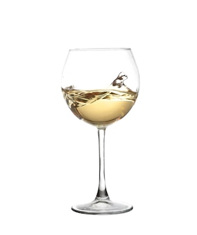 Vinho branco girando em uma taça de vinho, isolado em uma parede branca