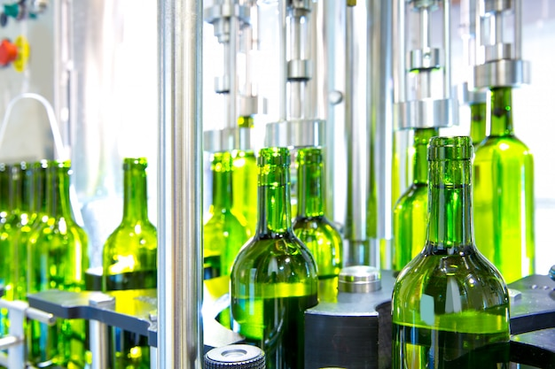 Vinho branco na máquina de engarrafamento na adega