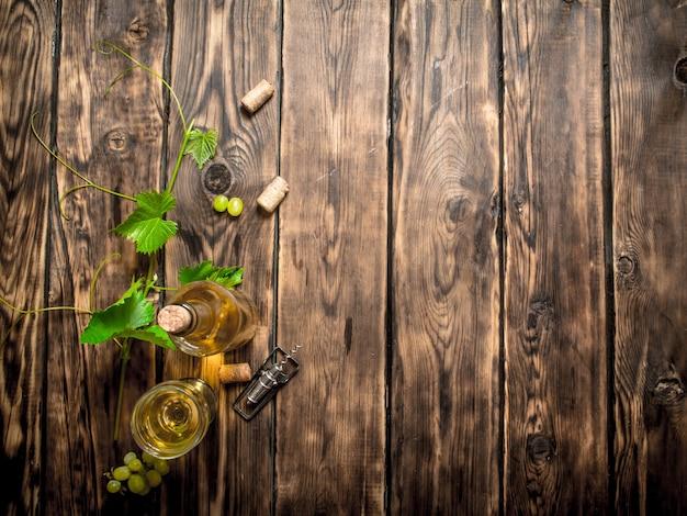 Vinho branco na videira na mesa de madeira.