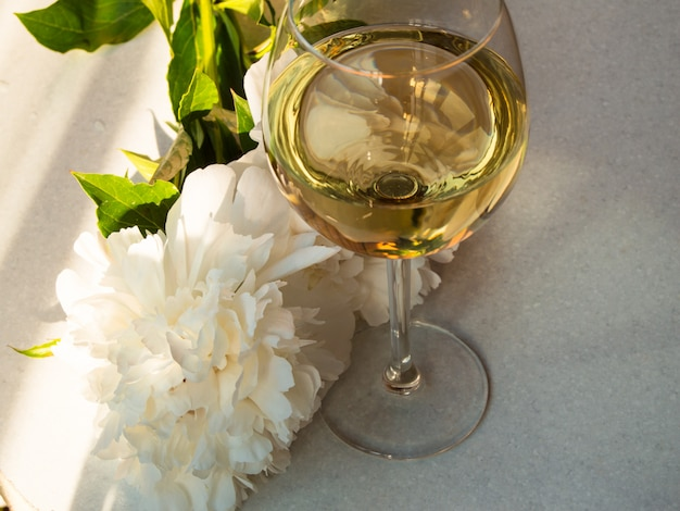 Vinho branco nas flores de vidro e peônia. jantar romântico