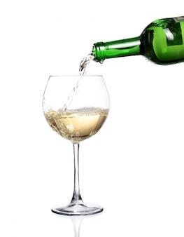 Vinho branco saindo da garrafa, introduza o copo no fundo branco
