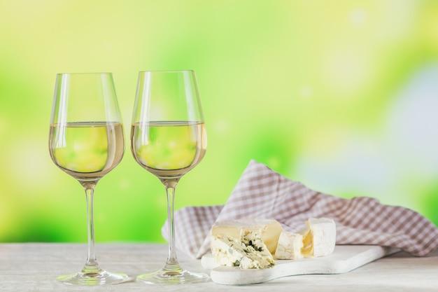 Vinho branco servido com prato de queijo numa superfície verde clara. duas taças de vinho verde. conceito de férias sazonais.