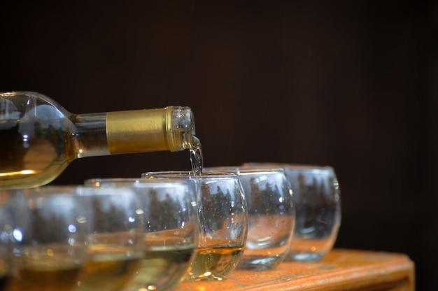 Vinho branco servido de uma garrafa em um copo