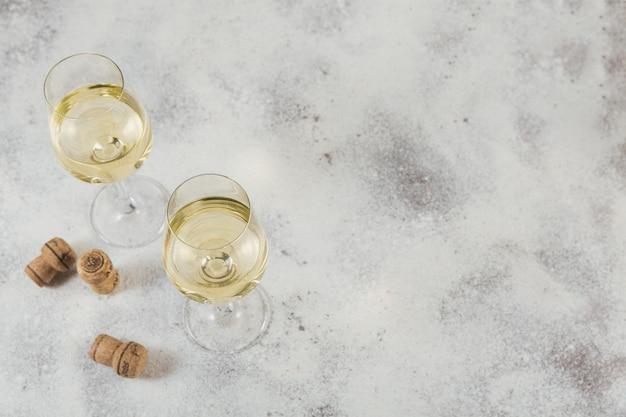 Vinho branco sobre superfície cinza claro. duas taças de vinho verde. conceito de férias sazonais.