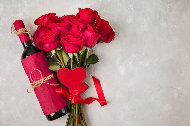 Vinho buquê de rosas e sinal de saúde na mesa cinza