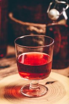 Vinho caseiro de frutas vermelhas em vidro na superfície de madeira