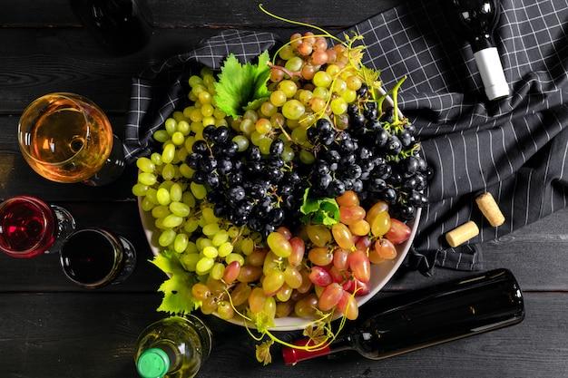 Vinho com galhos de uvas brancas. em uma mesa de madeira