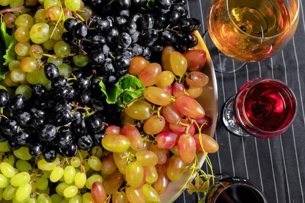 Vinho com ramos de uvas brancas. em uma mesa de madeira.