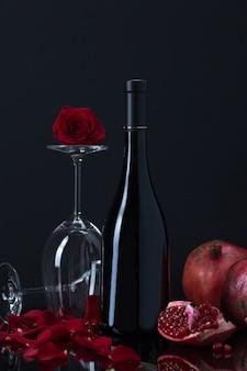 Vinho com taças, romãs e pétalas de rosa