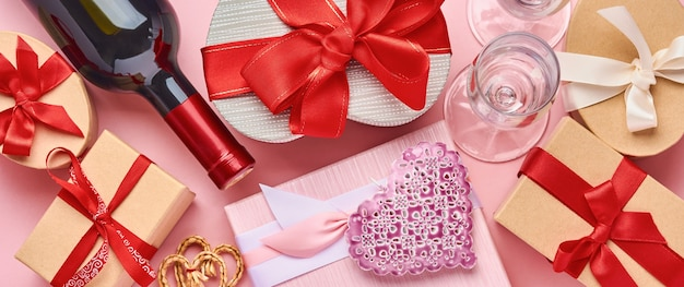 Vinho, copos e caixa de presente em forma de coração com uma fita vermelha em fundo rosa. cartão postal do conceito de dia dos namorados. bandeira. vista do topo.