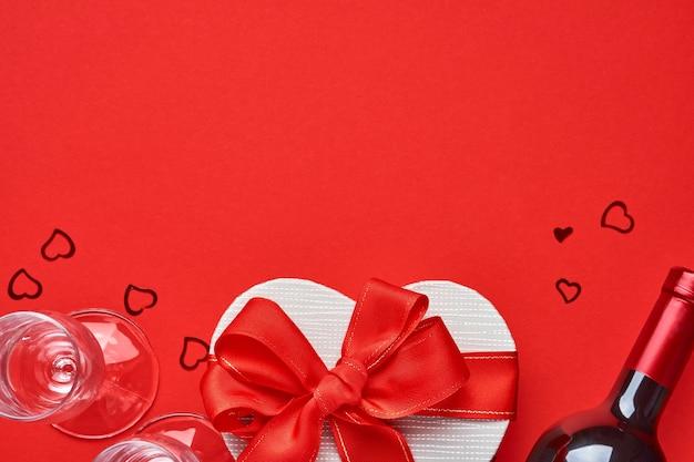 Vinho, copos e caixa de presente em forma de coração com uma fita vermelha sobre fundo vermelho. cartão postal do conceito de dia dos namorados.