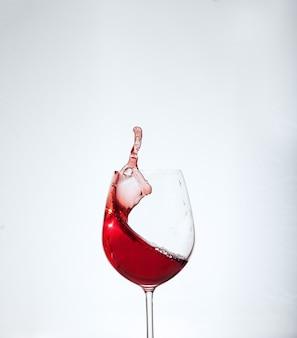Vinho de bordeaux no vidro em um fundo branco.