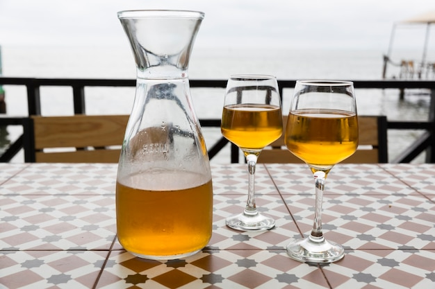 Vinho de laranja de kvevri. batumi, restaurante de tbilisi à beira-mar. uma jarra e dois copos. contra o fundo do mar