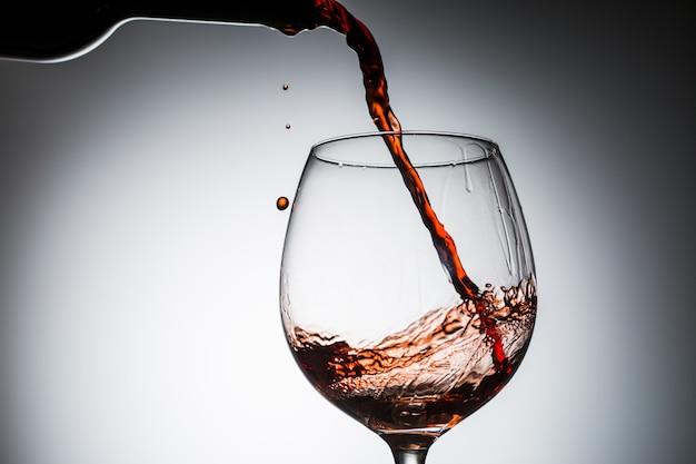 Vinho de uva derramado da garrafa em copo de vinho de vidro