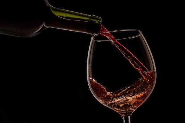 Vinho de uva derramado em copo de vinho sobre fundo preto