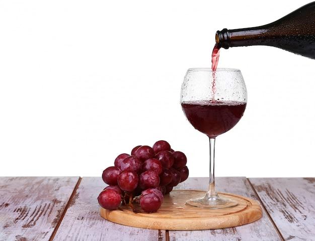 Vinho derramando em vidro com uva e garrafas isoladas