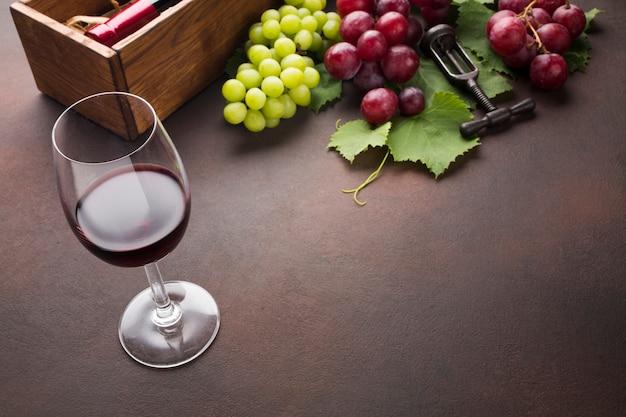 Vinho e deliciosas uvas no fundo