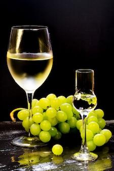 Vinho e grappa de vidro com cacho de uvas