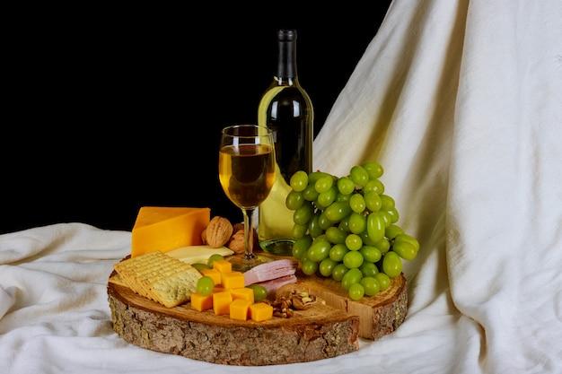 Vinho e variedade de queijo na mesa de madeira ainda-vida