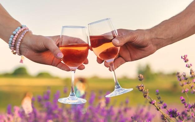 Vinho em taças é segurado por uma mulher e um homem em um campo de lavanda. foco seletivo. natureza.